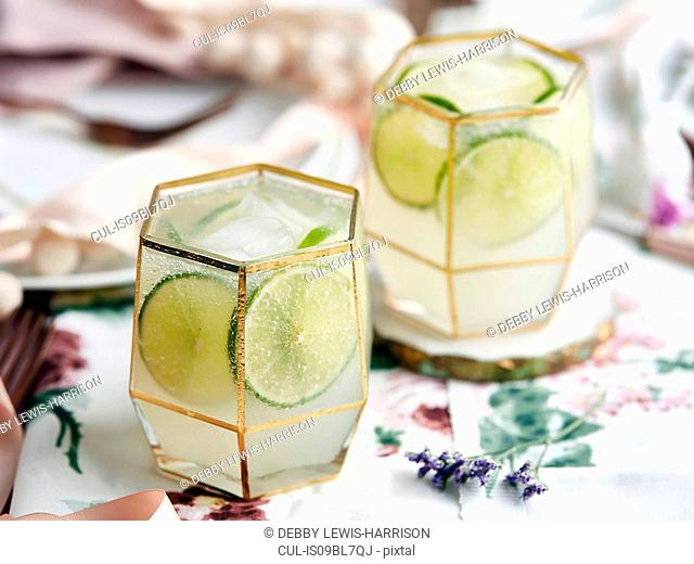 Cocktails with lime slices and ice cubes