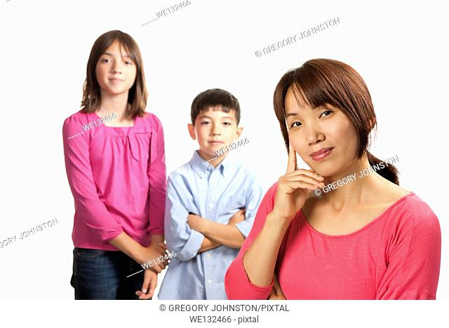 A concept portrait of a mother in the foreground and her two kids in the background