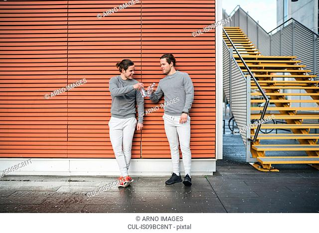 Young adult male twins training, raising a toast in urban setting