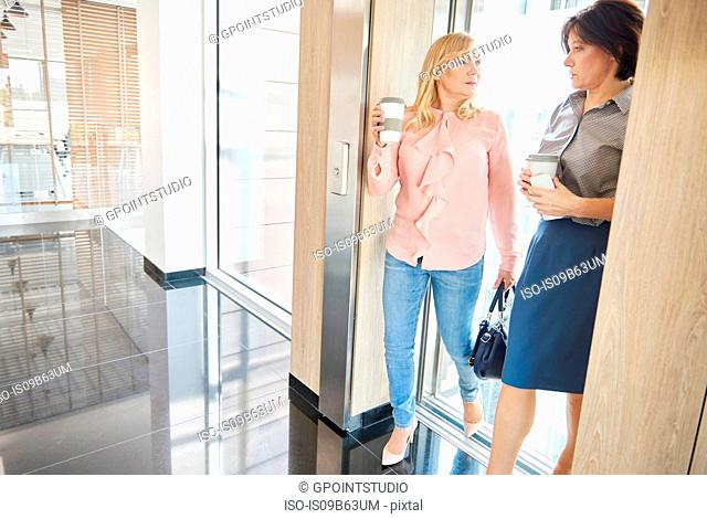 Colleagues in office building using lift