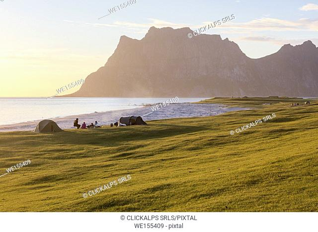 Camping tents on green meadows next to sea lighted up by midnight sun Uttakleiv Lofoten Islands Northern Norway Europe