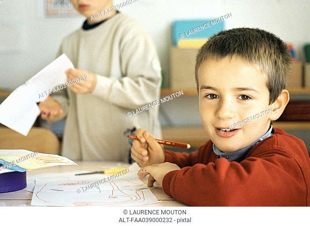 Boy drawing at desk, smiling at camera
