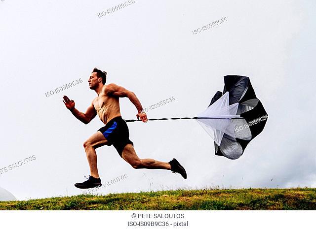 Man running, using running parachute
