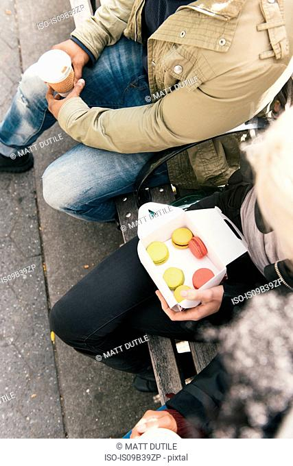 Cropped view of couple holding box of macaroons