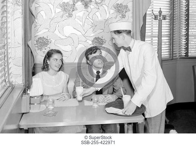 Waiter serving young couple in cafe