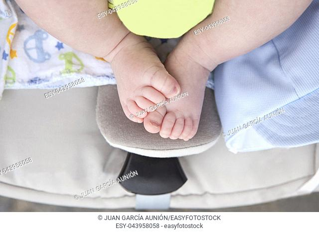 Newborn baby chubby feet over on i-size baby car over pushchair. Overhead shot