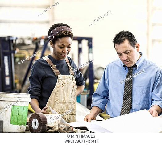 Hispanic man manager and black woman factory worker going over project plans in a sheet metal factory
