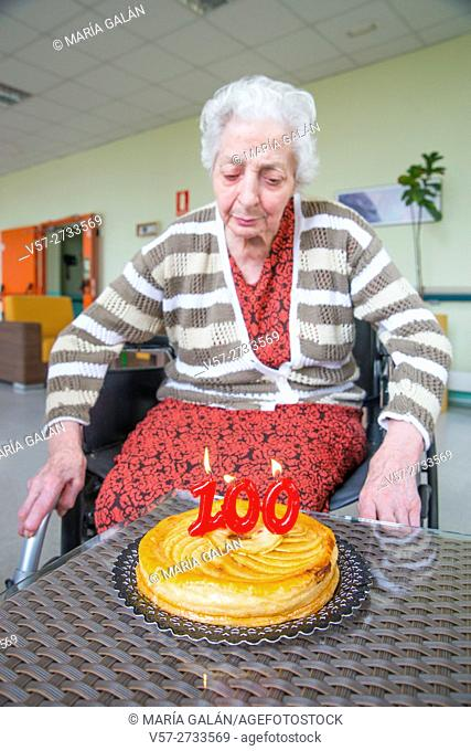 Old woman in a nursing home, on her one hundred birthday, blowing birthday's candles