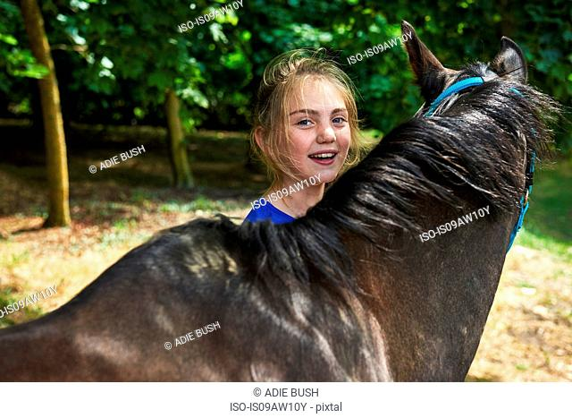 Head and shoulders of girl with horse looking at camera smiling