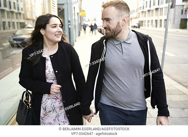couple walking at pavement in city, looking at each other