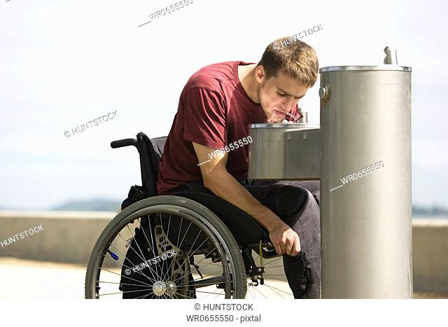 A young man on a wheel chair drinking water