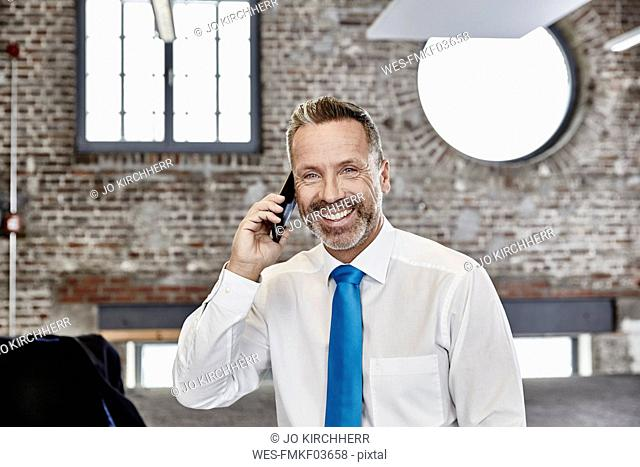 Smiling businessman on cell phone in a loft