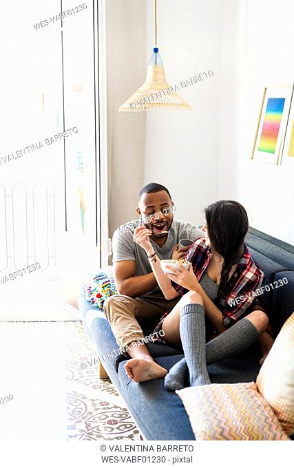 Young couple sitting on sofa, eating breakfast