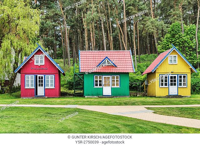 Three colorful wooden houses in the center of Nida. Nida (Nidden) is a village on the Curonian Spit to the Baltic Sea. The village is located on the lagoon side...
