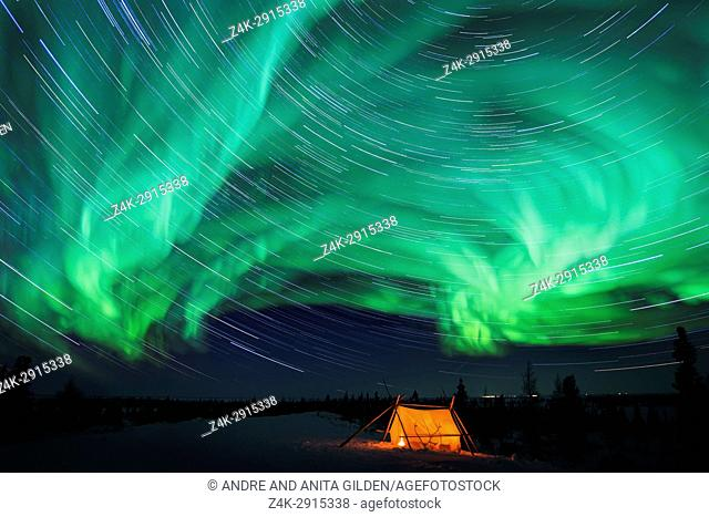 Nightsky and trappers tent lit up with aurora borealis, northern lights, and stars, wapusk national park, Manitoba, Canada
