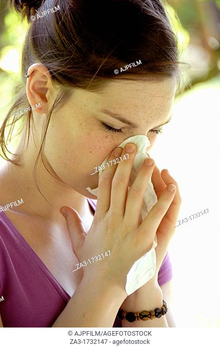 20 years old woman in a garden blowing her nose