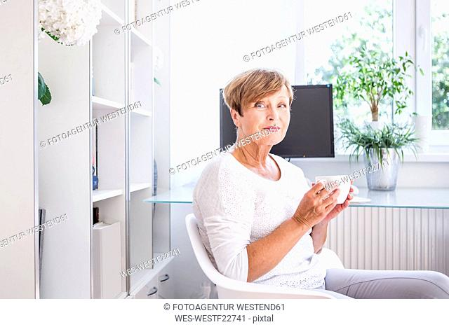 Portrait of senior woman drinking cup of coffee at home