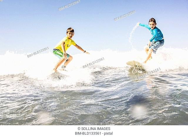Boys surfing in ocean