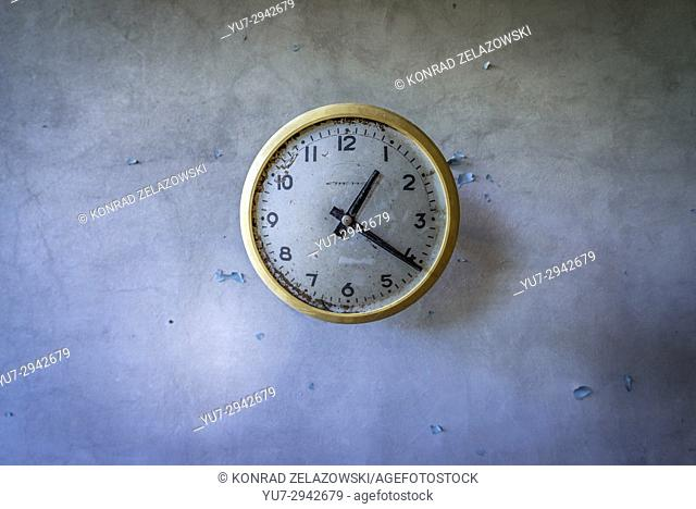 Old clock in abandoned Jupiter Factory in Pripyat ghost town of Chernobyl Nuclear Power Plant Zone of Alienation in Ukraine