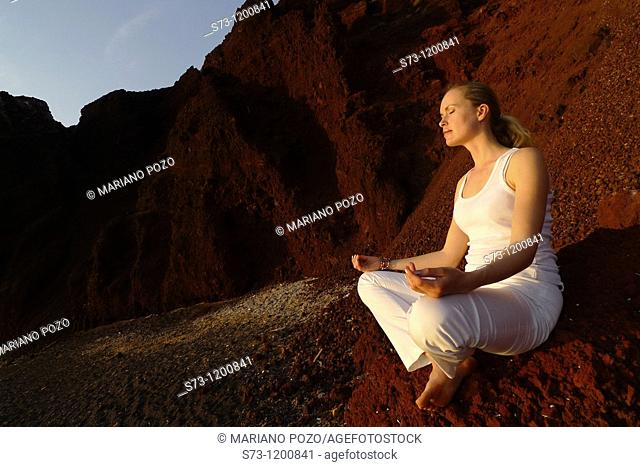 Young woman practicing yoga in the Red Beach in Santorini, Cyclades Islands, Greece