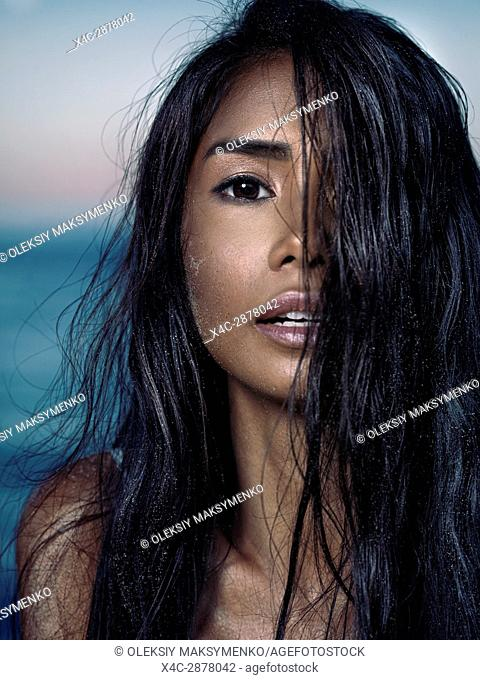 Sensual beauty portrait of a young asian woman with long wet dark hair full of sand particles covering her face with beautiful exotic features