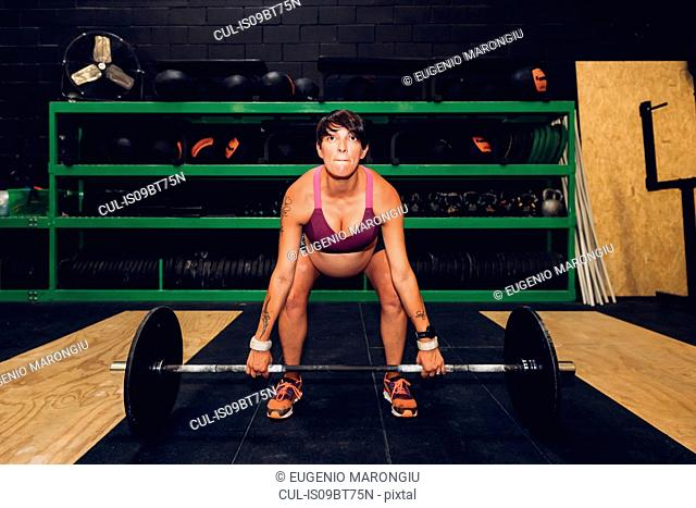 Pregnant woman using bar bell in gym