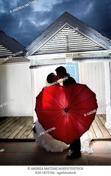 Wedding couple kissing with a red umbrella Ostia Rome Italy