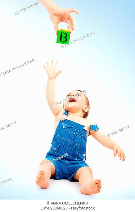 Happy child having fun, cute cheerful little boy stretches to take cube with the letters from mother's hand, studio shot, enjoying education