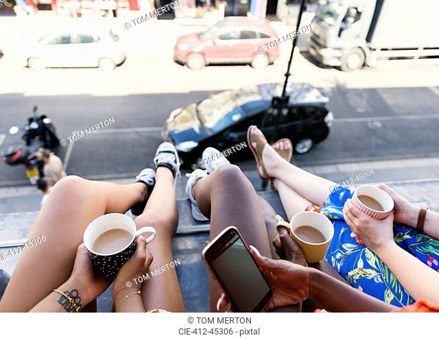 Women friends drinking coffee, dangling legs out urban apartment window