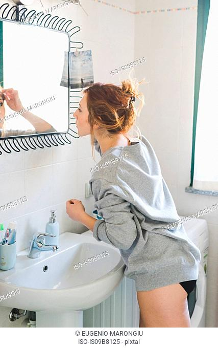 Young woman getting ready at bathroom mirror