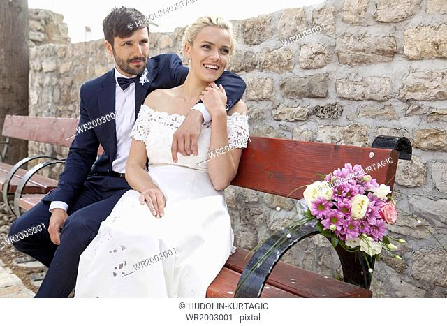 Bride and groom on bench smiling happily