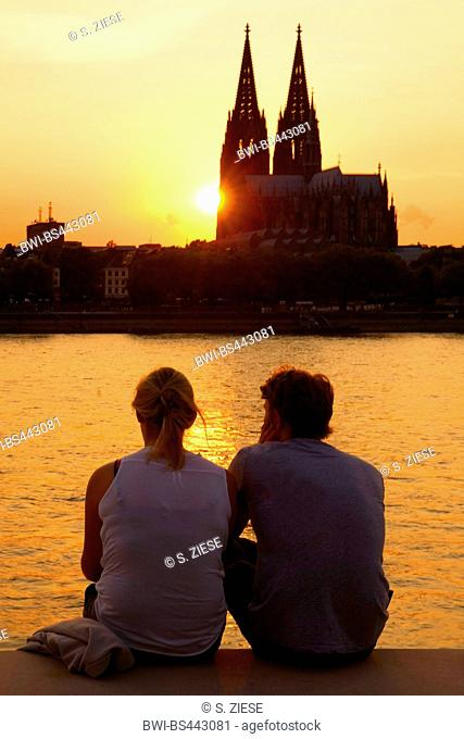 pair at the Rhine with Cologne Cathedral in the background at sunset, Germany, North Rhine-Westphalia, Cologne