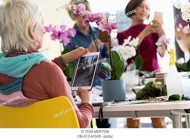 Active senior woman with digital tablet photographing orchid in flower arranging class