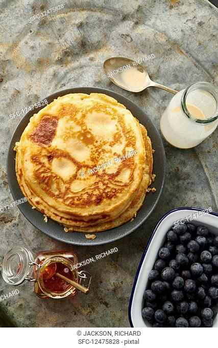 Pancakes, blueberries and maple sYesrup on a metal background