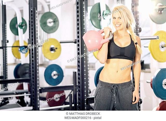 Young woman training with kettlebell in front of power rack at gym