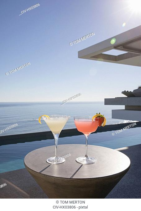 Cocktails in martini glasses on sunny luxury patio with ocean view