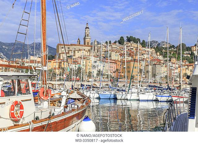 France, Alpes Maritimes, Menton, the Vieux Port with sailboats and the old town dominated by the Saint Michel Archange basilica