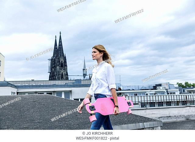 Germany, Cologne, young woman with pink skateboard on roof terrace