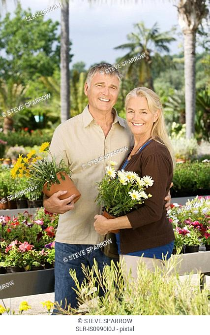 Couple with plants in garden centre