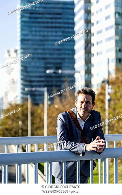 Relaxed businessman leaning on a railing, taking a break