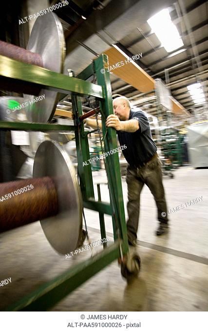 Textile worker setting up warp beams on weaving machine in carpet tile factory