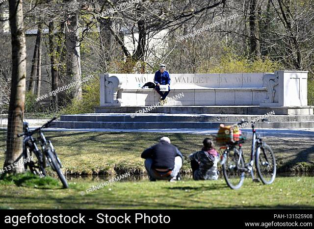 Public life in times of the coronavirus pandemic on April 5th, 2020 in the Englischer Garten in Muenchen. A man sits on Klenze's stone bench and reads a...