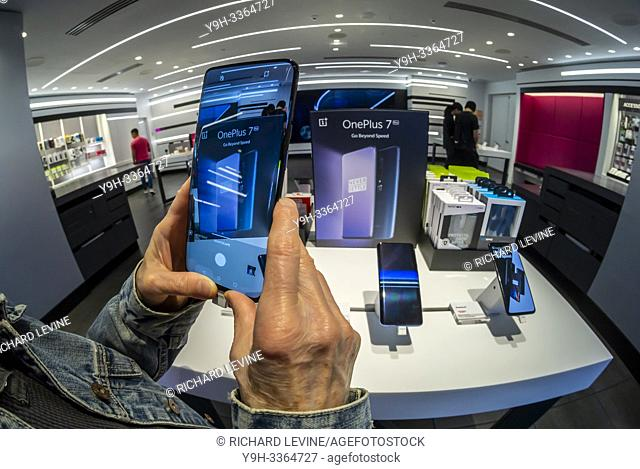 A visitor to a T-Mobile store in New York tries out the OnePlus 7 Pro smartphone on Thursday, May 16, 2019. The smartphone brand has a following which admires...