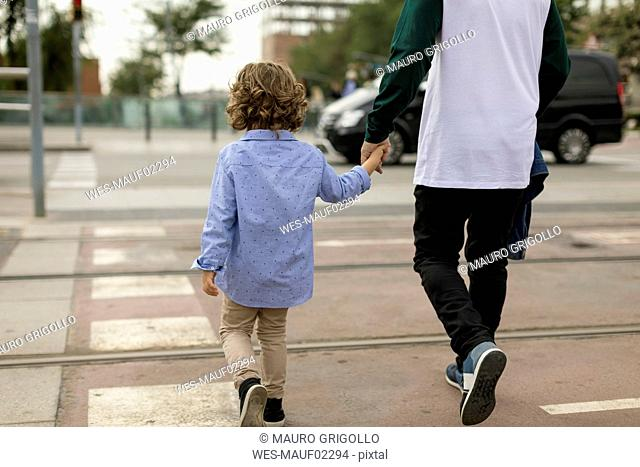 Rear view of father and son walking hand in hand in the city