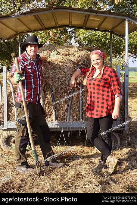 01 October 2020, Saxony, Wermsdorf: Cora Lechner stands in her bison enclosure with her life partner Johannes Boos at a storage place for organic hay