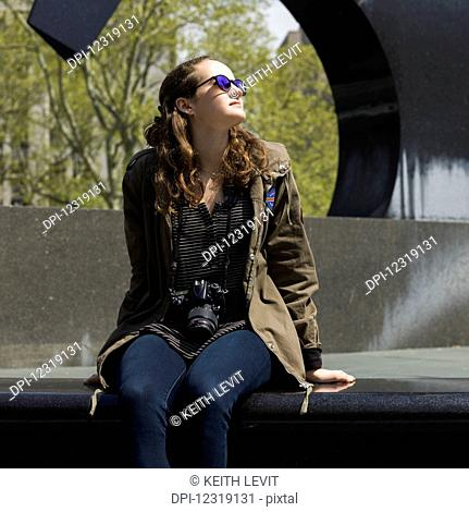 A woman sits on a bench in an urban park looking up with trees and a sculpture in the background; New York City, New York, United States of America