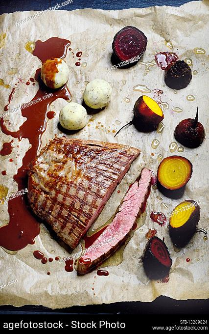 Flank steak with red and yellow beetroot with potato and poppy seed balls