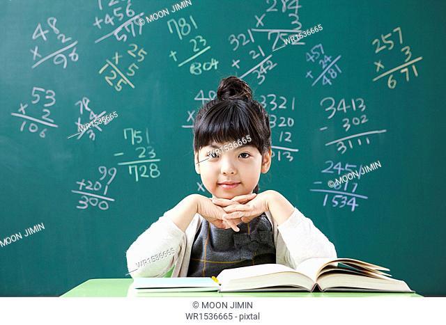 a girl doing math problems in a class room