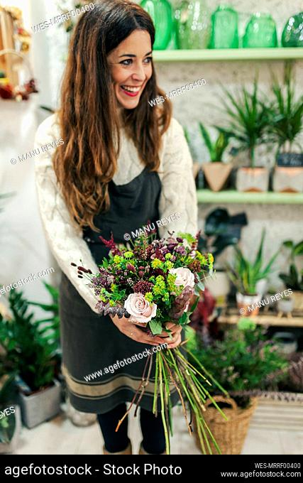 Smiling woman holding bunch of flowers while standing at flower shop