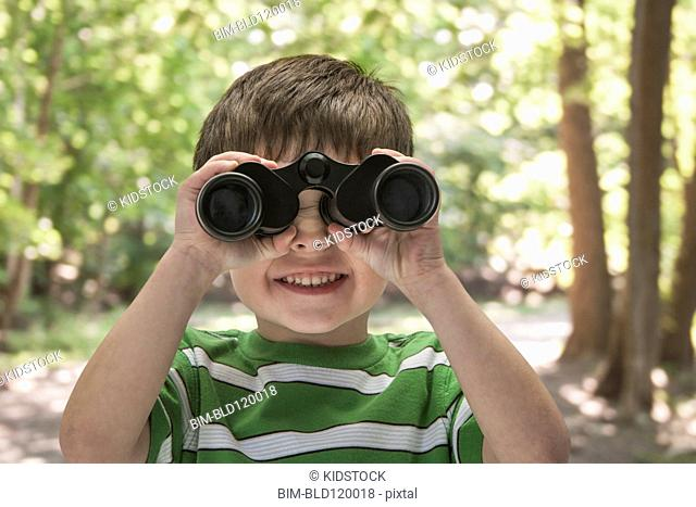 Boy using binoculars outdoors